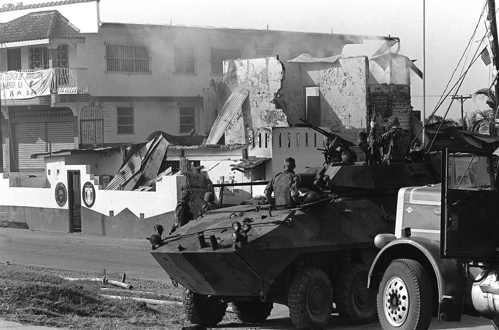 Marines of Company D, 2nd Light Armored Infantry Battalion, stand guard with their LAV-25 light armored vehicles outside a destroyed Panamanian Defense Force building during the first day of Operation Just Cause.