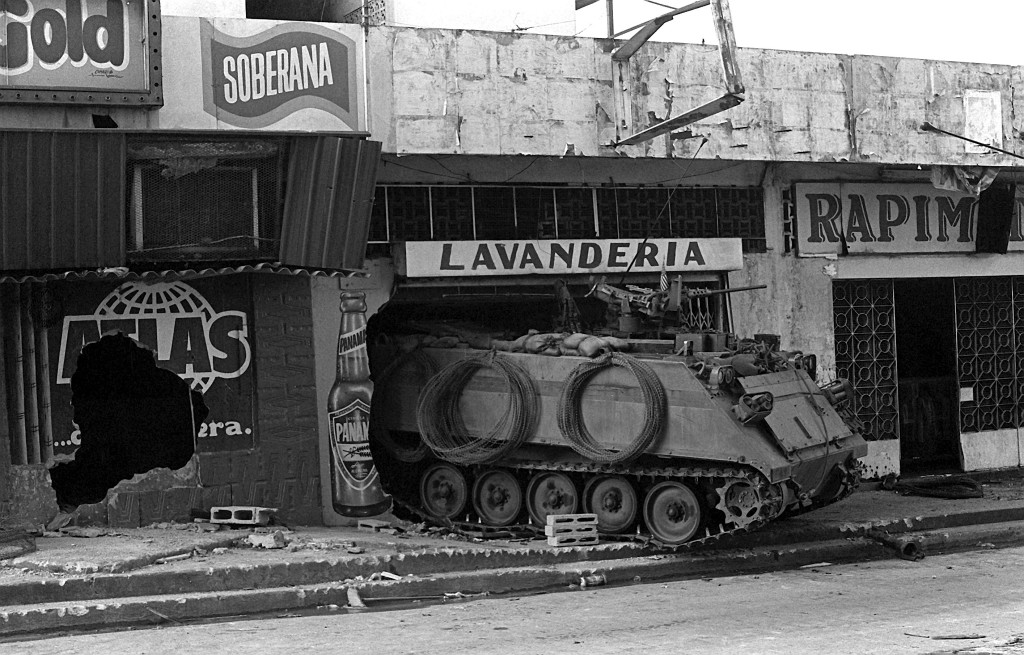 A U.S. Army M-113 armored personnel carrier guards a street near the destroyed Panamanian Defense Force headquarters building during the second day of Operation Just Cause.